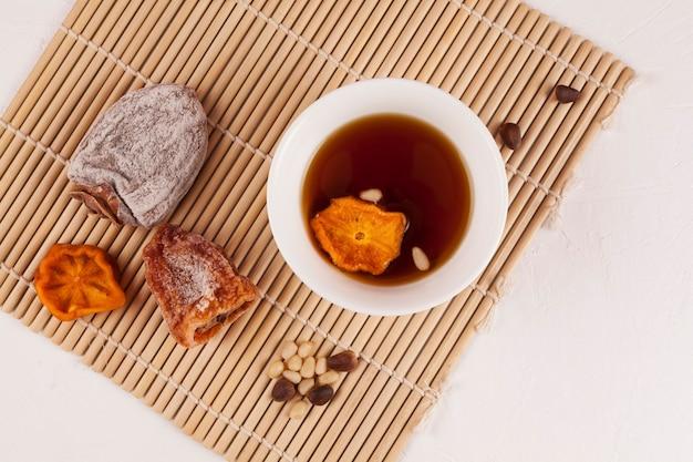 Sujeonggwa - chá gelado coreano. de cor marrom avermelhado escuro, é feito de gotgam (caqui seco) e gengibre e geralmente é decorado com pinhões.