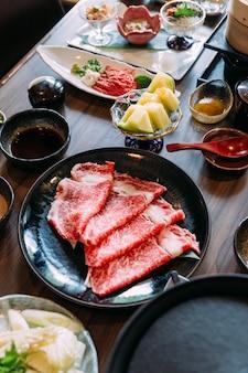 Sukiyaki grupo inclusive carne de boi de wagyu de fatias rara em uma chapa preta com o melão de honeydew japonês.