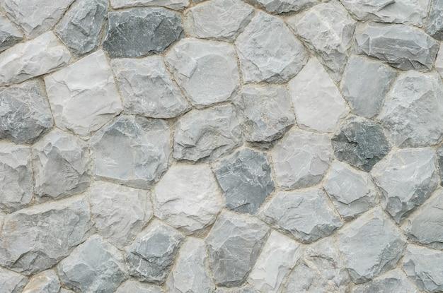 Sumário de superfície do close up na parede de pedra velha no fundo textured jardim