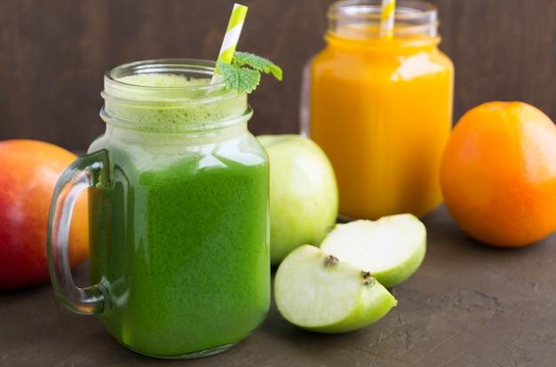 Sumos de fruta e vegetais úteis. no fundo escuro.