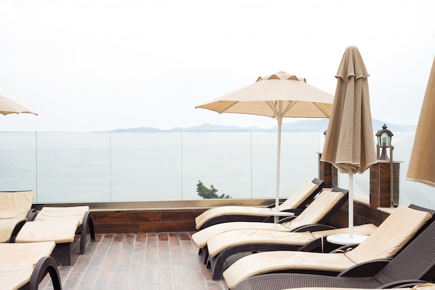 Sun guarda-chuvas cor bege e espreguiçadeiras perto da piscina com vista para o mar.