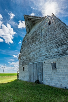 Sunburst sobre velho celeiro resistido nas pradarias com turbinas eólicas