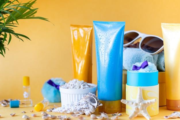 Suncare garrafas, copos, folhas de palmeira de estrela do mar sobre um fundo amarelo. beleza e cuidados no verão. copie o espaço