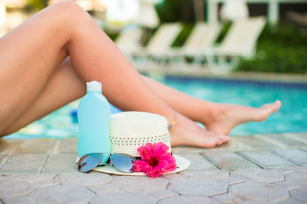 Suncream, chapéu, óculos de sol, flor e pernas femininas bronzeadas perto da piscina