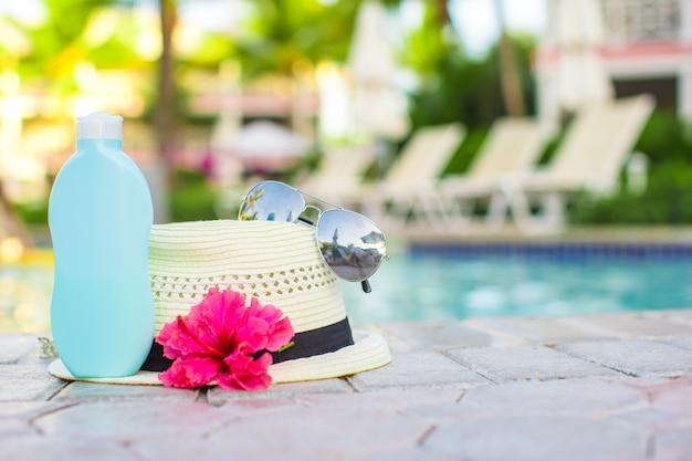 Suncream, chapéu, óculos de sol, flor e torre perto da piscina