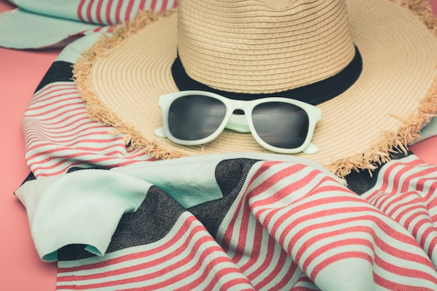 Sunhat da praia da palha e vidros de sol no rosa punchy.