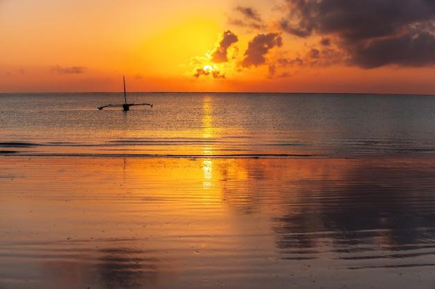 Sunrise over oceano índico barco de madeira na praia de mombaça com lindo nascer do sol no backgro