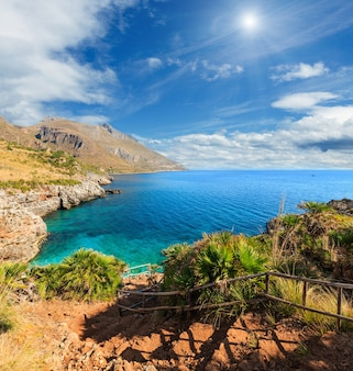 Sunshiny paradise beach bay com água azul e vista para a praia da trilha costeira do parque da reserva natural zingaro, entre san vito lo capo e scopello, província de trapani, sicília, itália