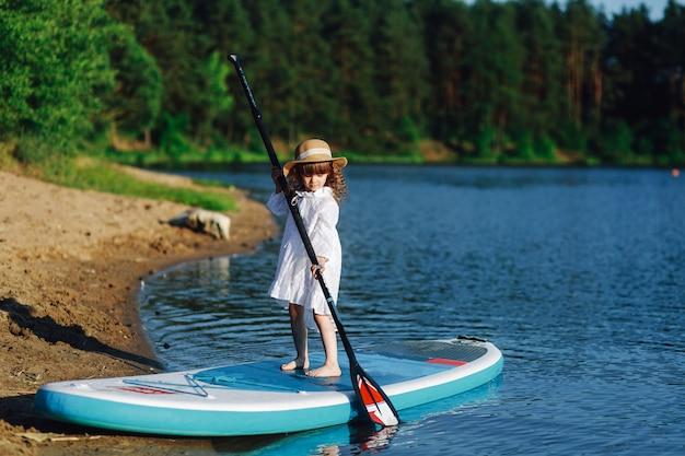 Sup a garota em um vestido branco com uma prancha flutua na água.