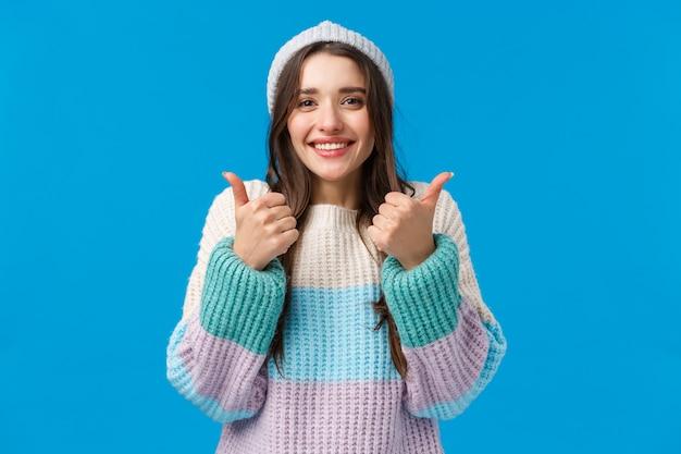 Super boa, idéia incrível. alegre alegre morena mulher bonita no chapéu do inverno, camisola, sorrindo e mostrando os polegares para cima em aprovação, incentive o amigo, diga parabéns ou sim, acene com a cabeça, parede azul