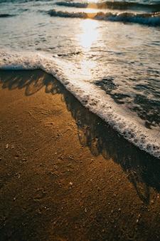 Super close de algumas marés com bolhas na praia durante um sol super colorido