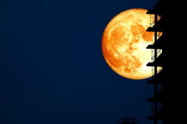 Super colheita de lua de sangue e construção de silhueta no céu noturno.