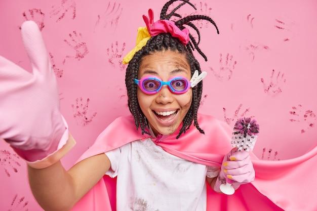 Super dona de casa feliz e ocupada com tranças usa óculos de proteção e luvas de borracha sorri positivamente segura a escova suja limpa a casa finge ser poses de super-herói contra a parede rosa