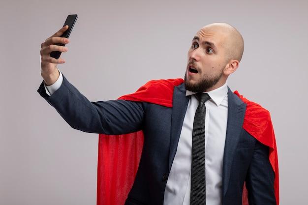 Super-herói barbudo homem de negócios com capa vermelha usando smartphon fazendo selfie sendo confuso em pé sobre uma parede branca