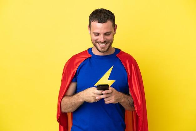Super herói brasileiro homem isolado em fundo amarelo enviando mensagem com celular