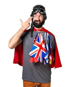 Super-herói com muitas bandeiras fazendo gesto de suicídio