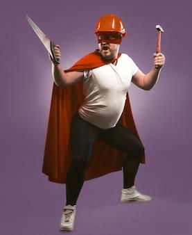 Super herói corajoso reparador ou faz-tudo com serra e martelo. engenheiro homem de capacete vermelho e super herói uniforme segurando ferramentas de construção isoladas em fundo roxo uva