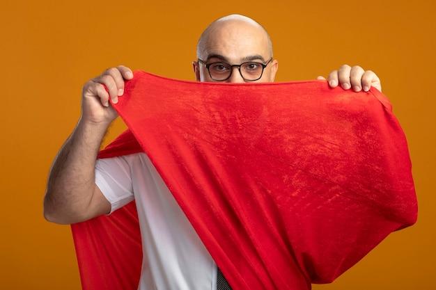 Super-herói empresário com capa vermelha e óculos com rosto sério cobrindo a boca com capa