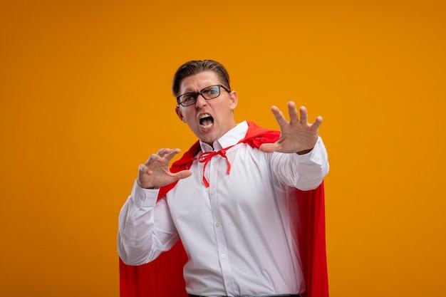Super-herói empresário com capa vermelha e óculos olhando para a câmera com os braços abertos, gritando com expressão agressiva, fazendo gesto de defesa em pé sobre um fundo laranja