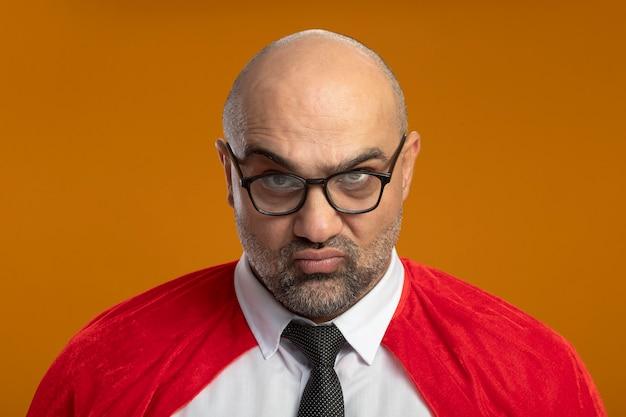 Super-herói empresário com capa vermelha e óculos olhando para a câmera com uma cara carrancuda descontente