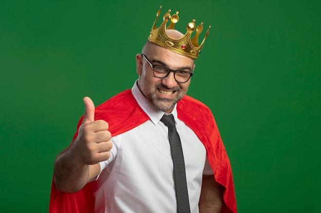 Super-herói empresário com capa vermelha e óculos usando coroa, olhando para a frente, sorrindo com uma cara feliz mostrando os polegares para cima em pé sobre a parede verde