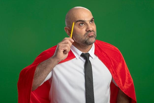 Super-herói empresário com capa vermelha segurando um lápis e coçando a cabeça, perplexo, parado em frente à parede verde