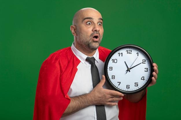 Super-herói empresário com capa vermelha segurando um relógio de parede olhando para o lado e ficando louco de espanto e surpresa em pé sobre a parede verde