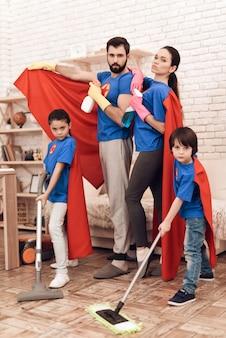 Super-herói feliz família limpeza casa com crianças.