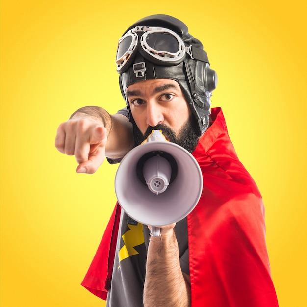 Super-herói gritando por megafone em fundo colorido