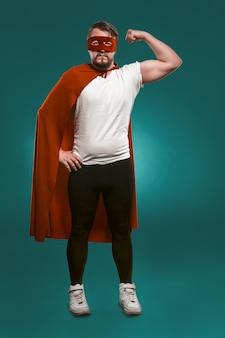 Super-herói homem mostra seus músculos e pronto para salvar o mundo. homem sério na máscara de super herói vermelho e casaco mostrando seus músculos, olhando para a câmera.