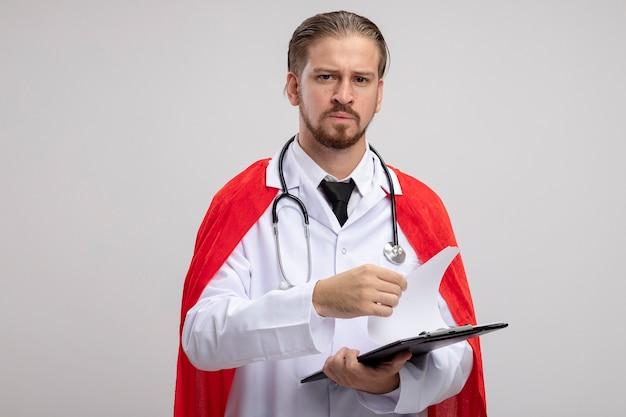 Super-herói jovem e confiante usando manto médico com estetoscópio folheando a prancheta