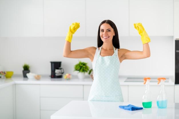 Super-herói para quartos sujos! garota de cabelos morenos usando luvas de borracha amarelas mostram que os músculos anunciam que ela pode limpar e polir todos os móveis da cozinha dentro de casa