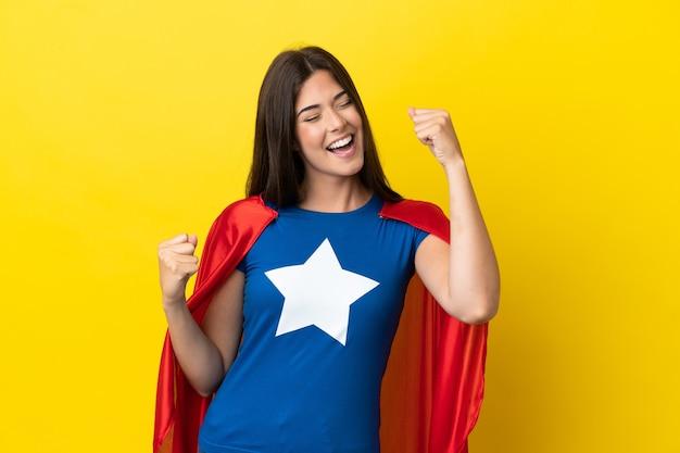 Super-heroína brasileira isolada em fundo amarelo comemorando vitória