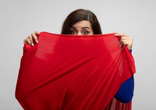 Super-heroína caucasiana chocada segurando e olhando para a câmera sobre a capa vermelha