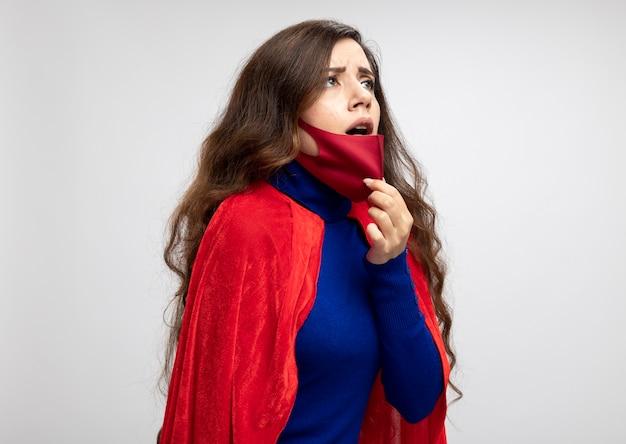 Super-heroína caucasiana sufocada com capa vermelha usando e puxando uma máscara protetora vermelha