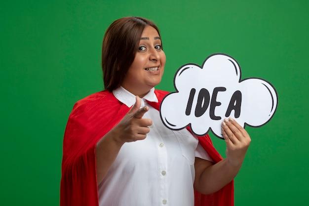 Super-heroína de meia-idade sorridente segurando uma bolha de ideias e mostrando um gesto isolado em um fundo verde