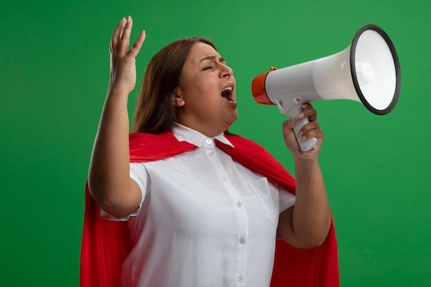 Super-heroína de meia-idade zangada com os olhos fechados falando no alto-falante e levantando a mão isolada sobre fundo verde