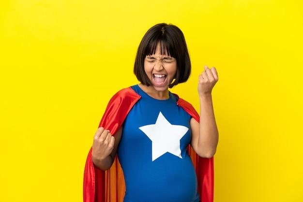 Super-heroína grávida isolada em um fundo amarelo comemorando uma vitória
