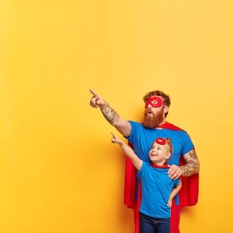 Super-heróis familiares fantasiados olham com interesse e surpresa para longe. papai assustado brinca com a filha pequena