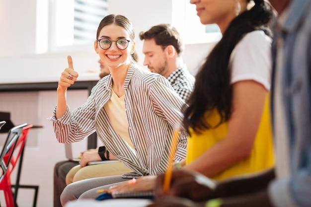 Super. menina emocional positiva sentada ao lado de seus colegas alunos e levantando o polegar depois de ouvir os resultados de seu exame