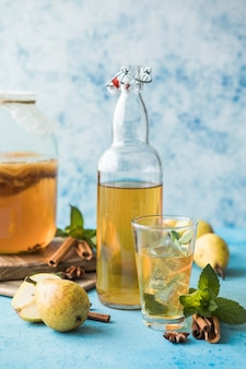 Superalimento cru fermentado de kombuchá, alcoólico ou não alcogólico. chá gelado com probiótico natural saudável em copo com hortelã no fundo azul