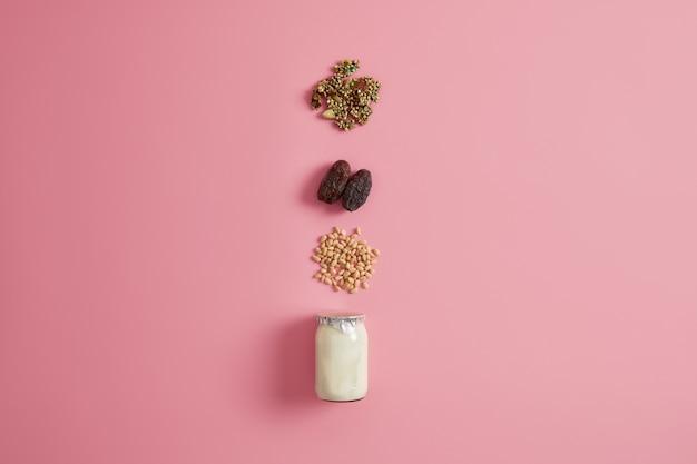 Superalimento, nutrição saudável e conceito de dieta. iogurte, nozes, frutas secas e sementes de abóbora para adicionar em sua sobremesa gourmet dietética. preparando lanche vegetariano. nutriente café da manhã orgânico