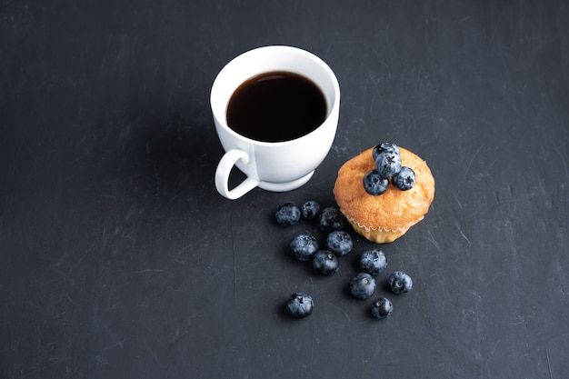 Superalimento orgânico antioxidante de mirtilo e bolinho doce com xícara de café conceito para alimentação saudável e dieta nutricional vista superior em fundo preto escuro