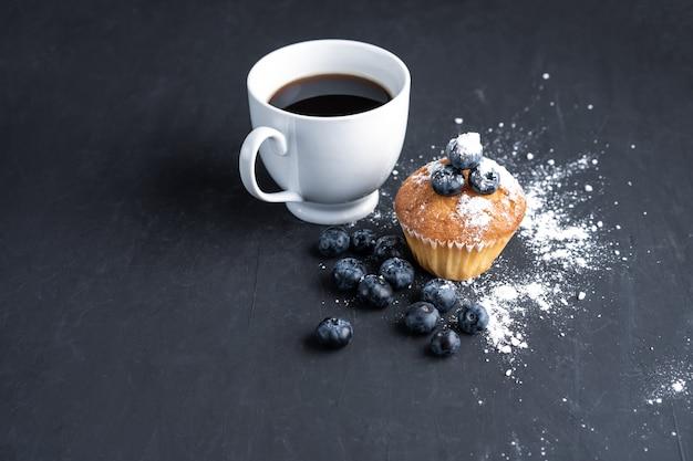Superalimento orgânico antioxidante de mirtilo e muffin doce com uma xícara de café para uma alimentação saudável e nutrição dietética vista superior em preto escuro