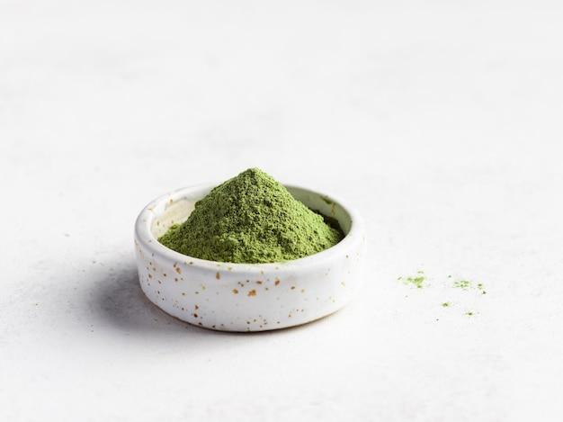 Superalimento verde em pó em uma tigela pequena. suporte de imunidade