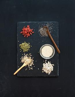 Superalimentos na lousa preta: bagas de goji, chia, feijão mungo, trigo sarraceno, quinoa, sementes de girassol. vista do topo