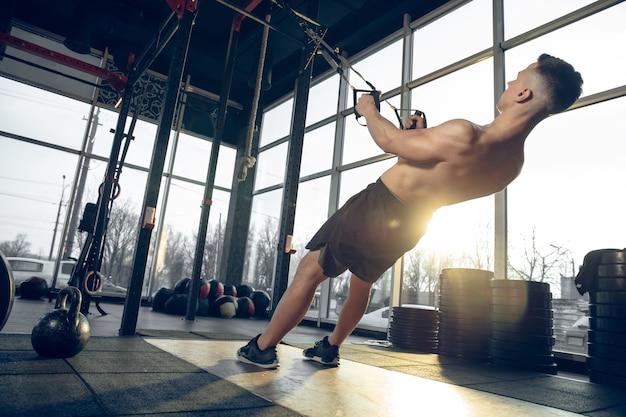 Superando. jovem atleta caucasiano musculoso treinando no ginásio, fazendo exercícios de força, praticando, trabalhando na parte superior do corpo com anéis de pesos. fitness, bem-estar, esporte, conceito de estilo de vida saudável.