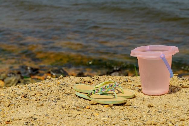 Superfície abstrata de viagens balde e chinelos na praia.