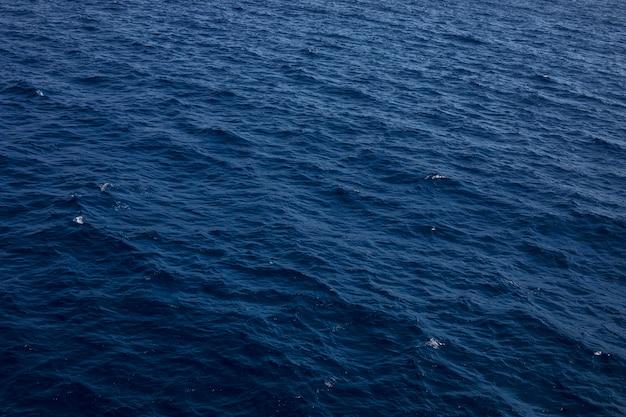 Superfície azul das ondas de água dos tons como o fundo. textura da água do mar.