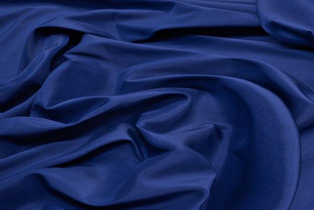 Superfície azul do tecido. fundo ondulante da textura do pano de fundo da roupa